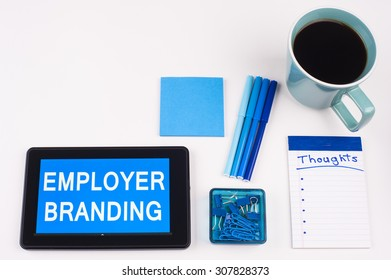 Business Term / Business Phrase on Tablet PC - Blues, cup of coffee, Pens, paper clips Calculator with a blue note pad on White - White Word(s) on blue - Employer Branding