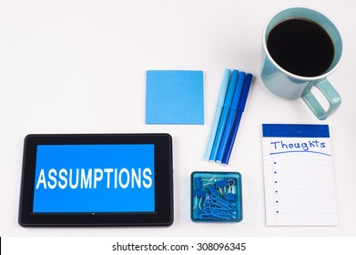Business Term / Business Phrase on Tablet PC - Blue Colors, Coffee, Pens, Paper Clips and note pads on White - White Word(s) on blue - Assumptions