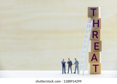 Business threat and SWOT analysis concept : Miniature figurine top management team e.g CEO, CMO and COO brainstorm and discuss on company or corporate sales / marketing strategy to retaliate a rival
