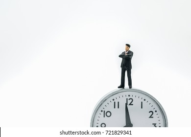 Business and time concept. Businessman miniature figure standing on vintage round watch on white background.