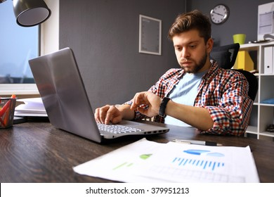 Business and time management concept. Stressed business man looking at wrist watch. Worried face expression. Human emotion