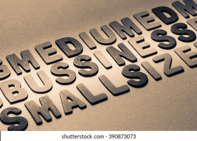 Business topic in the row of wood letters with part of Medium and Small Size word (SMB)