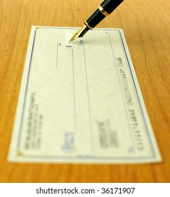 business transaction using a check, shallow focus on the pen tip