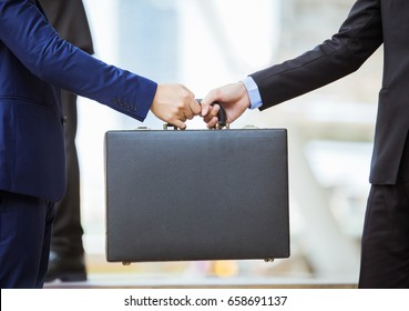 business transfer deal. handover of a suitcase in the hands of partners.