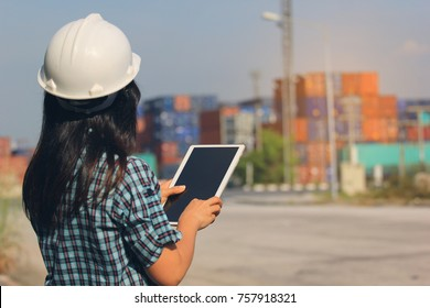 Business transportation of international logistics concept, Engineer holding digital tablet on front container and import export background