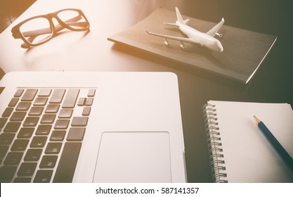 Business travel agency objects and equipment on computer working desk in vintage toning. Office desk with plane and computer for Business travel concept.