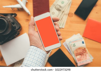 Business travel app for mobile phone mock up screen, overhead view of male business person hand using smartphone with blank screen as copy space