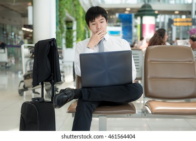 Business travel concept - Asian business man using a laptop in the waiting room of the airport.Technology in airport.