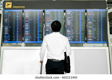 Business travel concept - Asian young business man with luggage waiting for travel in airport near flight timetable.
