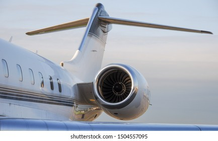 Business travel concept. Jet engine on parked luxury private jet. Rear detail with engine, tail-plane and windows of business-jet aircraft. Space for text.
