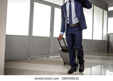 Business travel concept. Stylish businessman wearing formal clothes is going along airport lounge with his luggage. Copy space in the left side