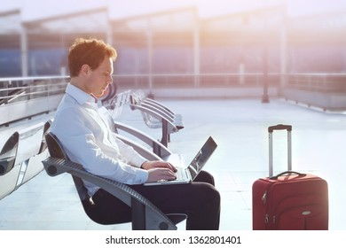 business travel, man in airport with laptop computer