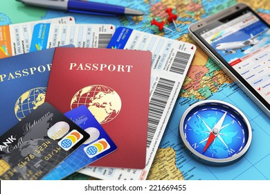 Business travel and tourism concept: air tickets or boarding pass, passports, smartphone with online airline tickets booking or reservation internet app, compass, credit cards and pen on world map