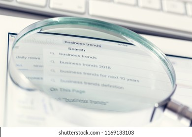 Business trends search concept. Magnifier enlarges the search window.