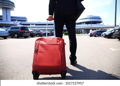 Business trip. Close-up of businessman carrying suitcase while walking through a passenger boarding bridge