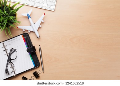 Business trip concept. Accessories on desk table. Pc keyboard, passport, notepad, calendar and airplane toy. Top view with copy space