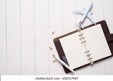 Business trip concept. Airplane and blank open notebook for your text.