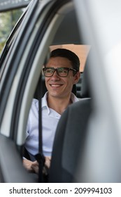 Business trip. Confident young businessman sitting in car and smiling