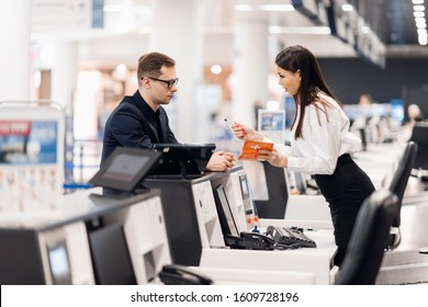 Business trip. Handsome young businessman in suit holding his passport and talking to woman at airline check in counter in the airport