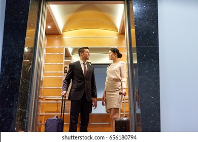 business trip and people concept - man and woman with travel bags in hotel elevator