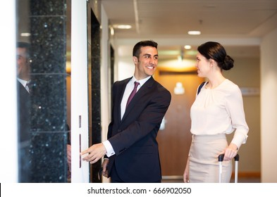 business trip and people concept - man and woman with travel bags at hotel elevator