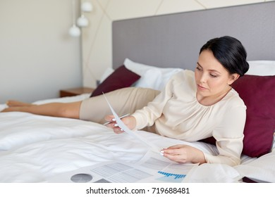 business trip, people and paperwork concept - businesswoman with papers working at hotel room