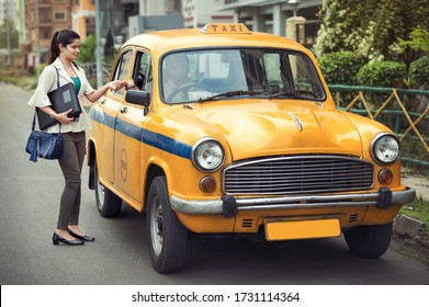Business trip, transportation, travel, gesture and people concept - Young girl giving fare to taxi driver after reaching office.
