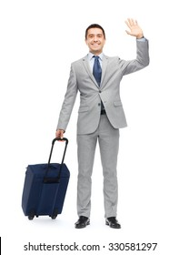 business trip, traveling, luggage, gesture and people concept - happy businessman in suit with travel bag waving hand
