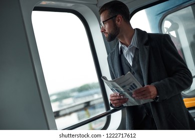 Business trip. Young businessman standing in the train holding newspaper looking out the window enjoying window view