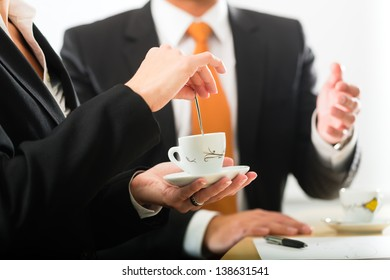Business - Two businesspeople or professionals have a conversation in an office drinking coffee or espresso