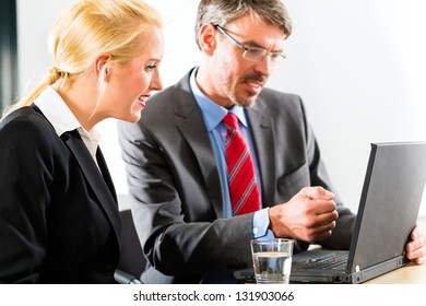 Business - Two professionals in office in business attire looking at laptop screen working together
