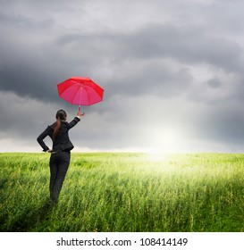 Business umbrella woman standing to rainclouds in grassland with red umbrella