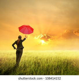 Business umbrella woman standing to sunset in grassland with red umbrella