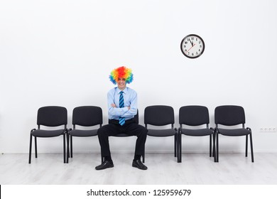 Business as unusual - businessman with clown hair sitting on row of chairs