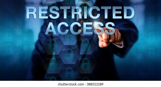Business user pushing RESTRICTED ACCESS on a touch screen interface. Information technology concept for data security mechanisms, encryption software and ransomware scams locking down computer files.