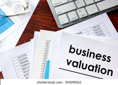 Business valuation written in a document and business charts.