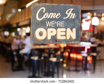 A business vintage sign that says 'Come in We're Open' on Cafe / Restaurant window. Image of abstract blur restaurant with people. Restaurant with customer for background usage