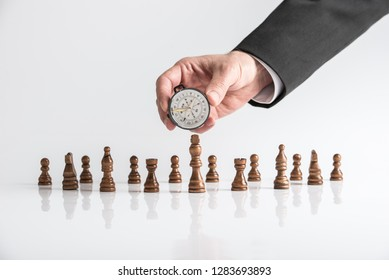 Business vision and direction concept - hand of a businessman holding a compass over chess pieces placed on white desk with reflection.