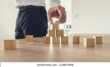 Business vision and idea concept - businessman standing at his office desk making pyramid of blank wooden blocks.