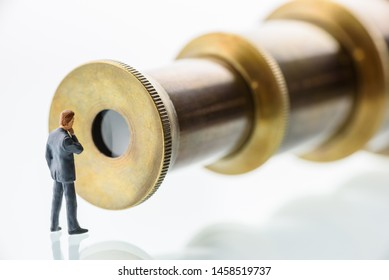 Business vision, searching for new challenge mission and growth opportunity concept : Miniature figurine businessman / top management person looks into a brass monocular telescope or retro spyglass