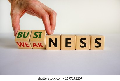 Business or weakness symbol. Businessman hand turns wooden cubes and changes the word 'weakness' to 'business'. Beautiful white background, copy space. Business or weakness concept.