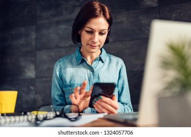 Business wearing denim shirt woman using smart phone at work