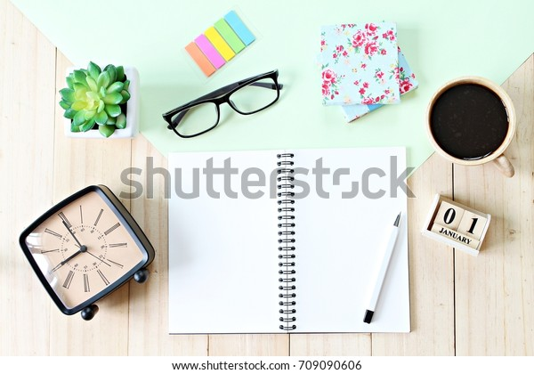 Business, weekend, holiday or new year planning concept : Top view or flat lay of open notebook paper, accessories, cube calendar and coffee cup on wooden background, ready for adding or mock up