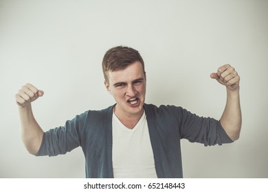 Business Winner Concept - Screaming Young Man a Funny Face and Open Mouth With Raised Arms