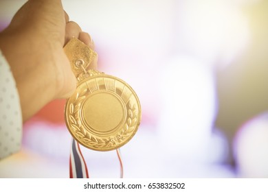 Business winner holding medal gold award to colorful background