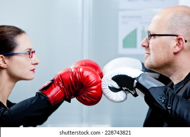 business and woma facing-off with boxing gloves