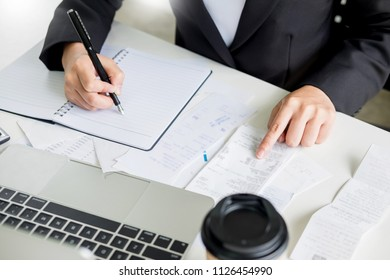 business woman accountant or banker making calculations Bills. doing finances in the office, economy concept through laptop.