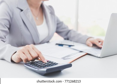 Business woman or accountant or banker making calculations. Savings,Business Financing Accounting Banking and economy Concept. ,Image of female hands using calculator on desk about cost on office.