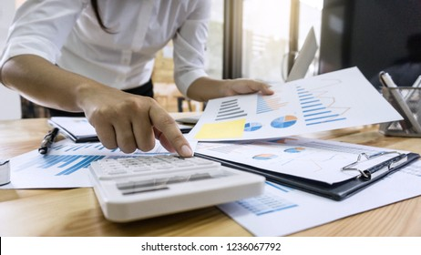 Business woman accountant working and calculating financial data on graph documents, doing finance in workstation.