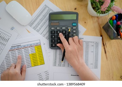 Business woman accounting concept financial in office and using a calculator to calculate the numbers on his desk in a office.